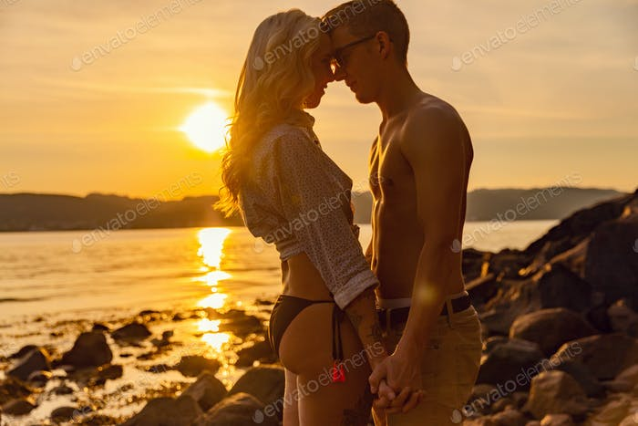 Young Romantic Couple Holding Hands At Beach During Sunset