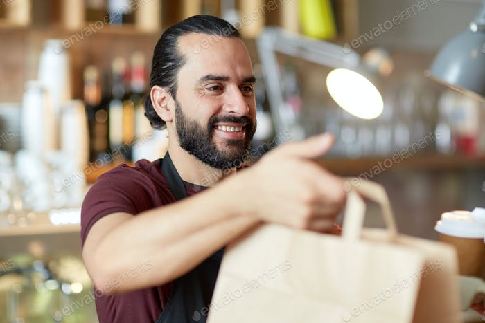 man or waiter with coffee and paper bag at bar