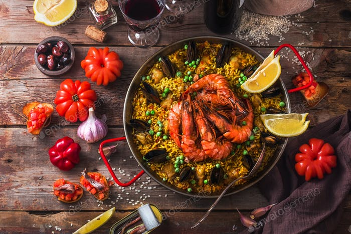 Top view of paella with prawns, mussels and lemon, wooden background