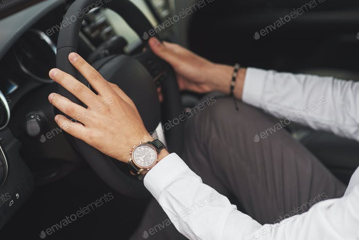A businessman rides his car, moves on the wheel. Hand with watch
