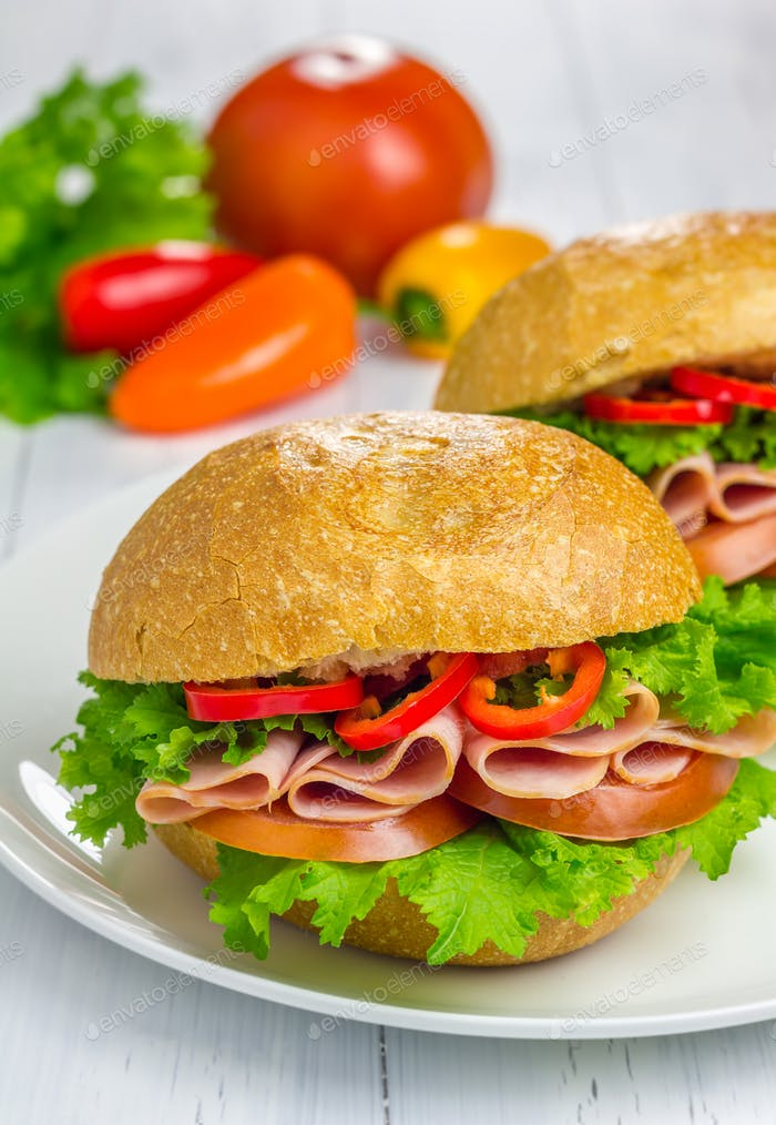 Healthy ham sandwiches with vegetables on background
