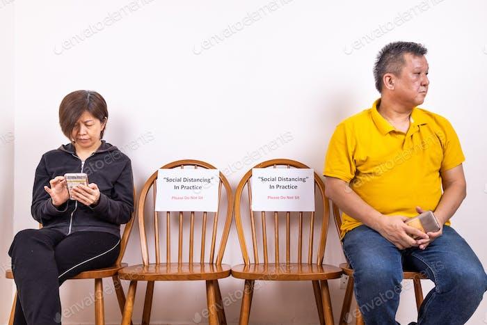 Menschen mit sitzen zwischen zwei Stühlen am öffentlichen Platz mit Social Distancing, Do Not Sit Beschilderung.