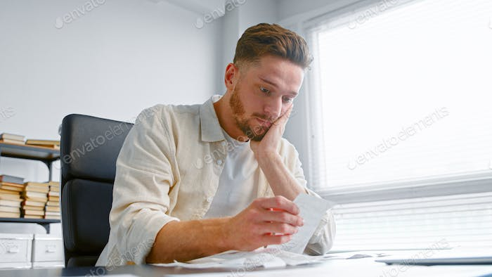 Shocked man bank accountant with beard looks at paper checks and puts hand on head