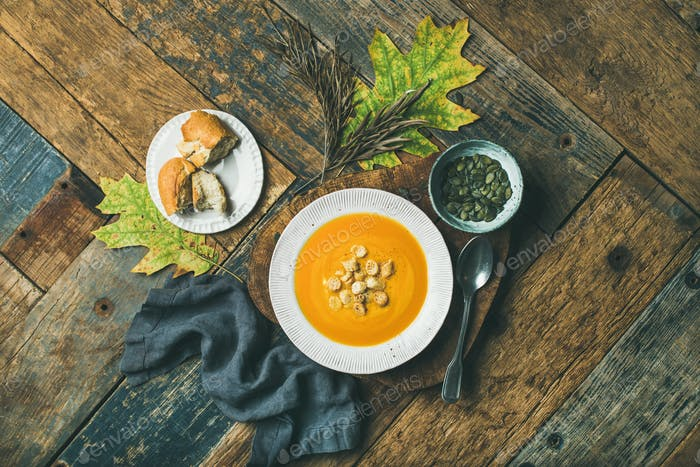Warming pumpkin cream soup with croutons and seeds, top view