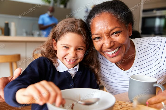Porträt von Großeltern in Küche mit Enkelin Essen Frühstück vor dem Gehen Zur Schule