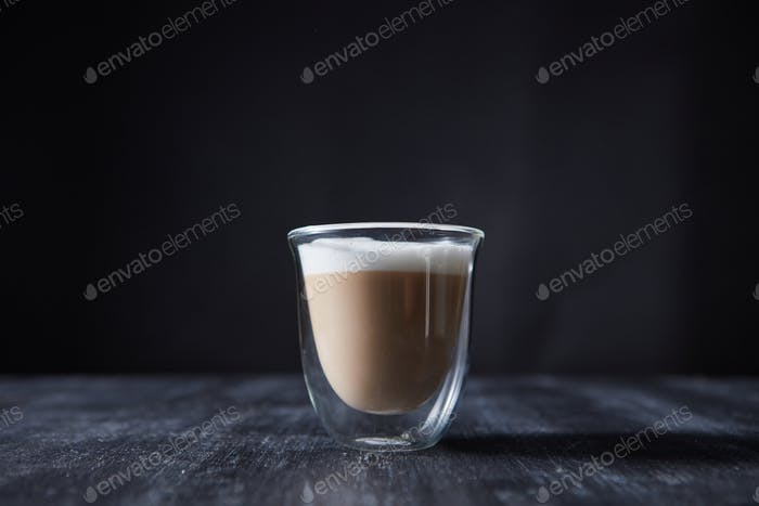 A glass cup of freshly made cappuccino presented on a black wooden table with copy space