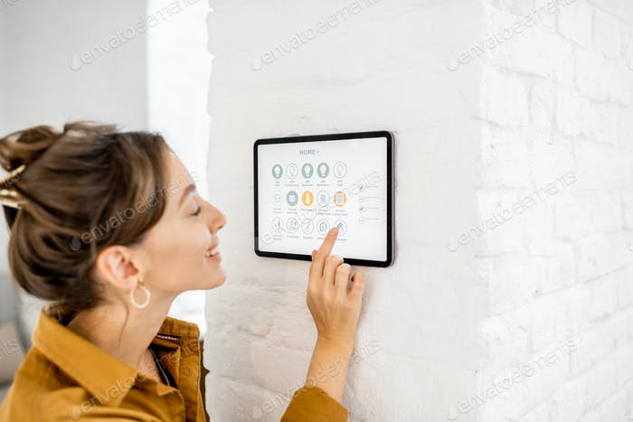 Frau Steuerung zu Hause mit einem digitalen Touchscreen