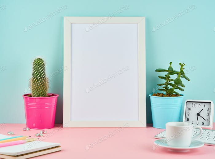 Mockup with blank white frame, alarm, notepad, cup of coffee or tea on pink table
