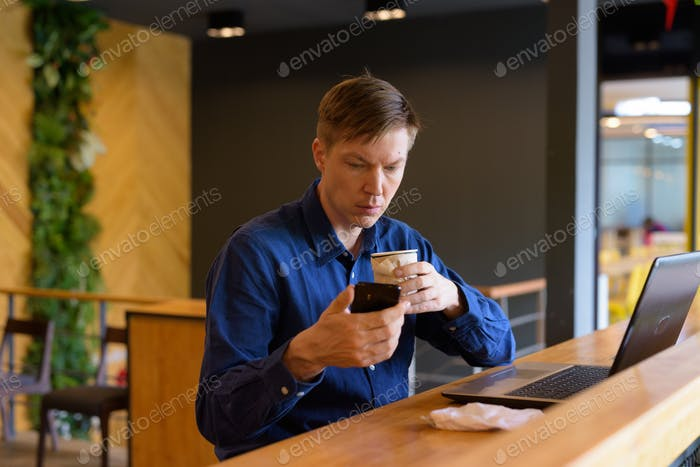 Young handsome businessman with coffee using phone and sitting with distance at the coffee shop
