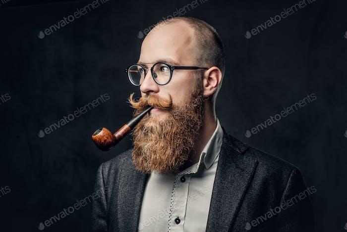 Мужчина курит трубу на сером фоне.