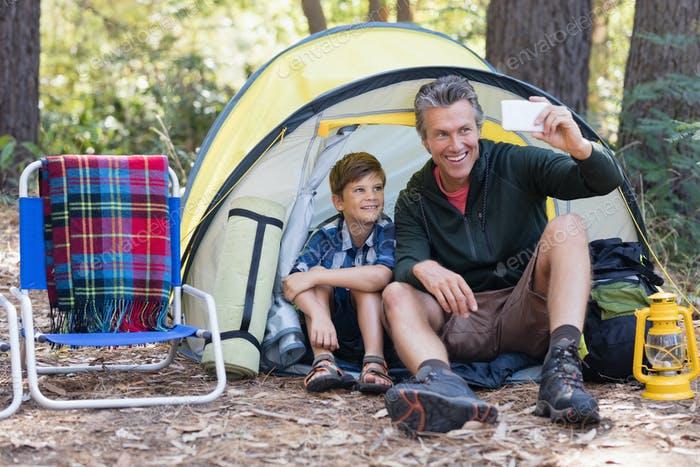 Father and son taking selfie while sitting in tent