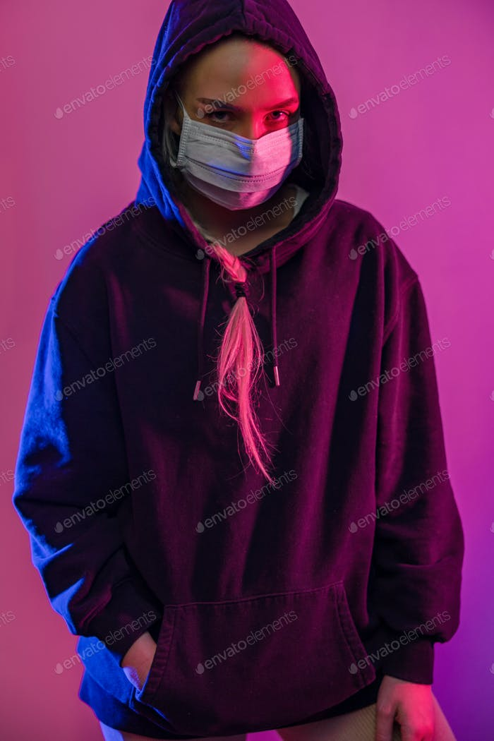 Cool looking young woman in protective face mask with multi colored lights
