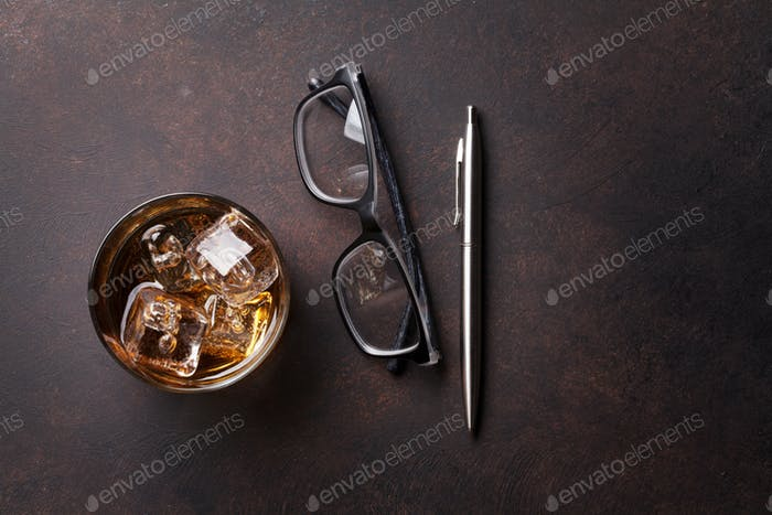 Whiskey with ice, pen and eyeglasses