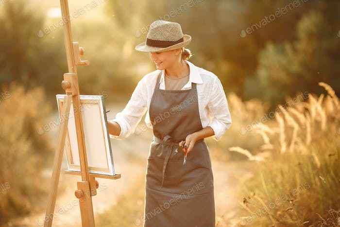 Woman in a apron painting in a field