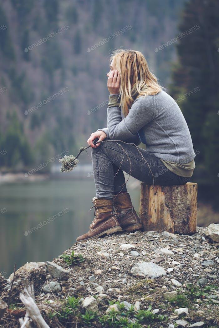 woman meditating on a lake shore