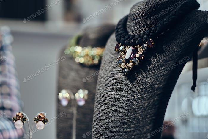 Halsketten mit Edelsteinen auf einer schwarzen Schmuckbüste in einem Geschäft.
