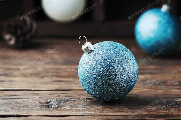 White and blue christmas balls on the wooden table