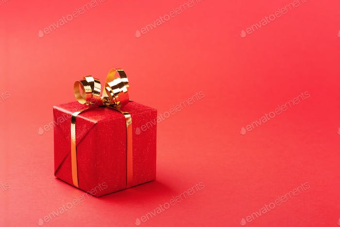 Red Gift Box with Golden Bow on Red Background