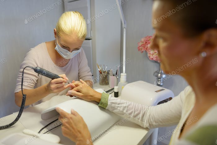Young woman beautician with mature woman getting manicure