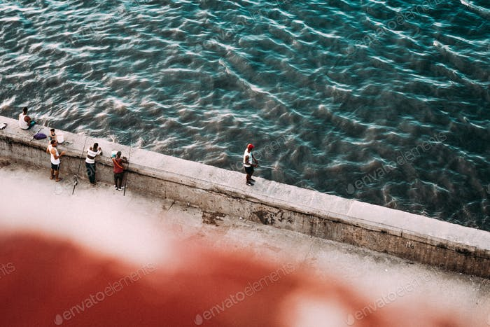 Fishers on concrete seafront from above