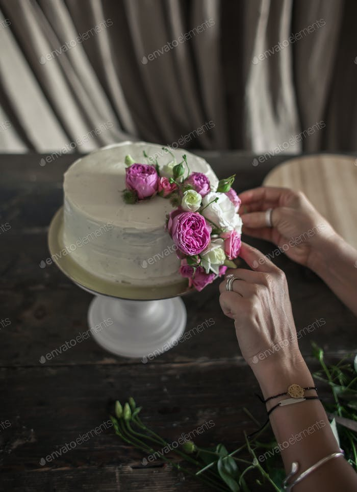 female decorating cake with flowers