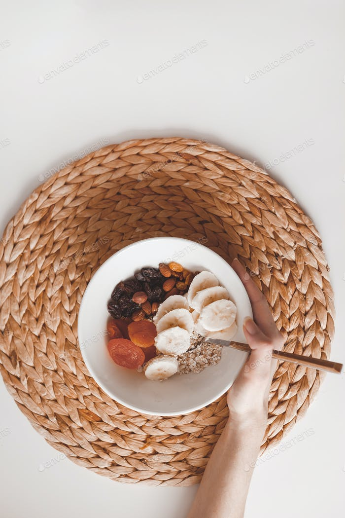 Carbohydrate healthy breakfast oatmeal with dried fruits on a white plate. View from above