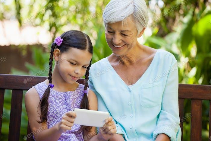 Lächeln Senior Frau Blick auf Mädchen mit Handy