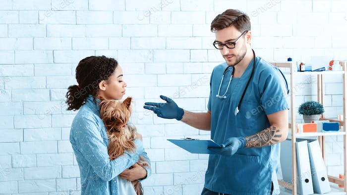 Dog owner with her cute pet communicating to veterinary doctor at medical office