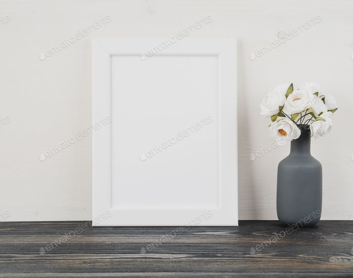 White frame, flower in vase, clock on dark grey wooden table against white wall with copy space