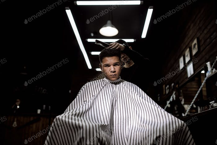 The stylish barbershop. The fashion barber makes a stylish hairstyle for a black-haired man sitting