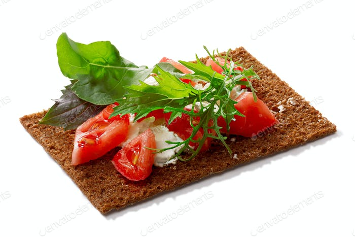 Bread crisp with tomato, soft cheese and greens
