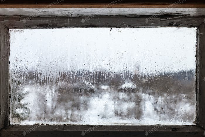 water drops from melting ice on frozen window