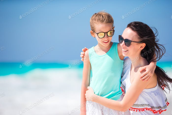 Portrait of little adorable girl and young mother at tropical beach