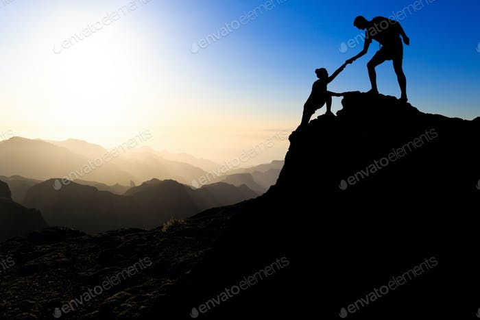 Teamwork couple hiking helping hand