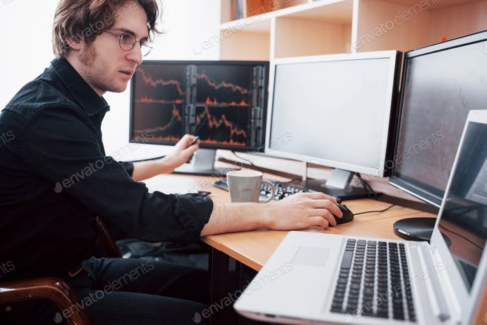 Young businessman holding hands on his face while sitting at the desk in creative office