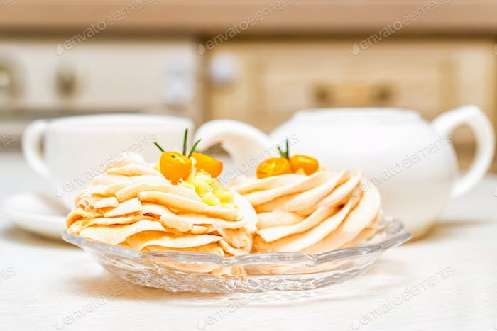 Meringue cake decorated with kumquat and tea