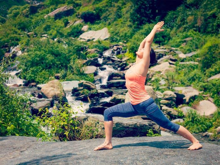 Frau tut Ashtanga Vinyasa Yoga Asana Virabhadrasana 1 Krieger