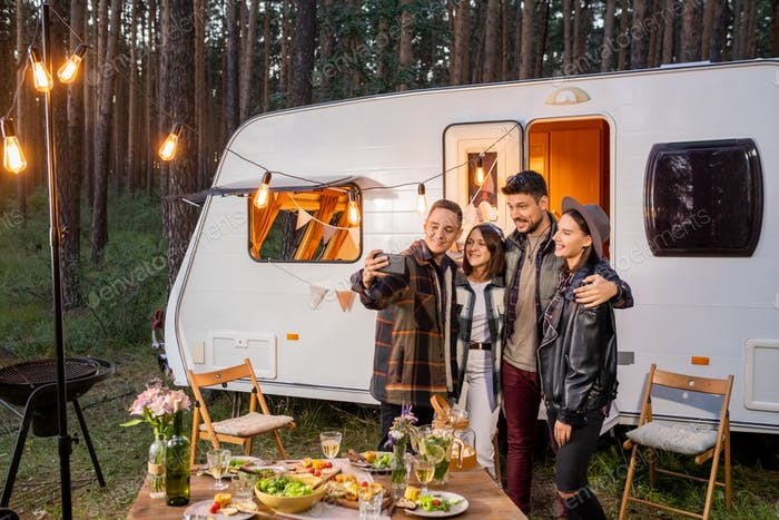 Group of happy young friends making selfie by mobile house