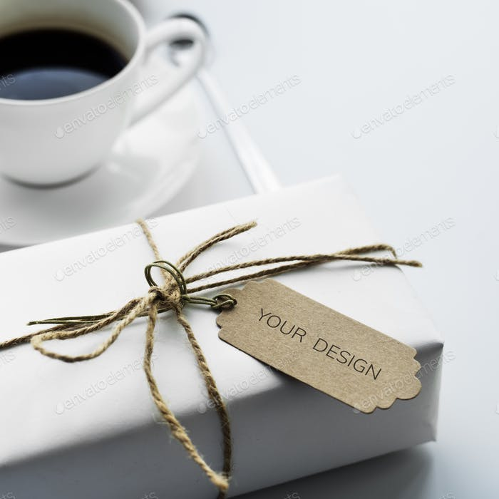 Closeup of gift box with empty label tag and coffee cup