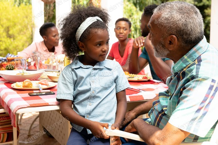 African American girl sitting on her grandfather knees during a family lunch in the garden