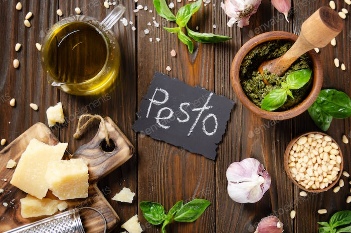 Food background of genovese pesto sauce in wooden mortar and its ingredients on kitchen table