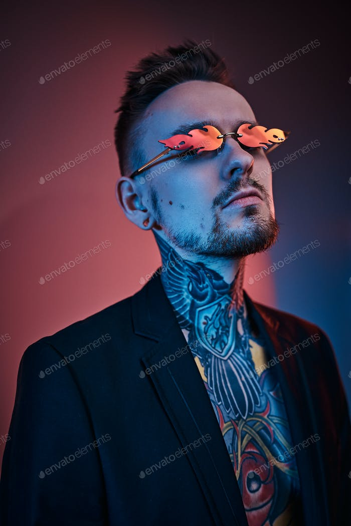 Tattoo artist male model posing in a neon studio with half-naked body, tuxedo and sunglasses.