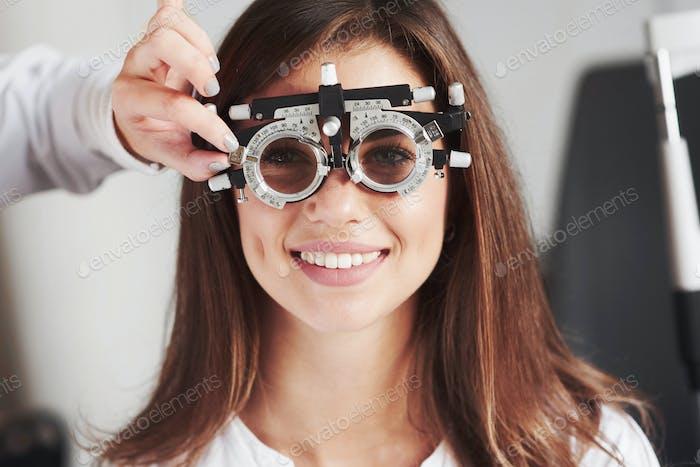 Attraktive Mädchen lächelnd, während tragen Phoropter, die Melodie von Arzt bekommen