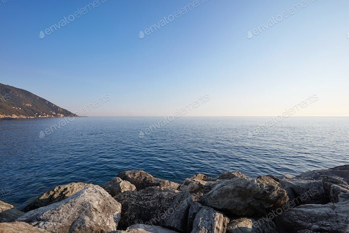 Mediterranean blue, calm sea with rocks and coast, clear sky