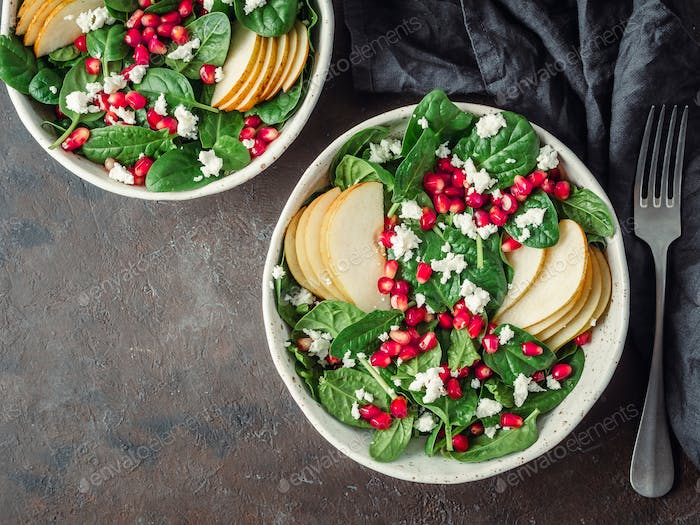 Vegan salad bowl with arugula, pear, pomegranate, cheese