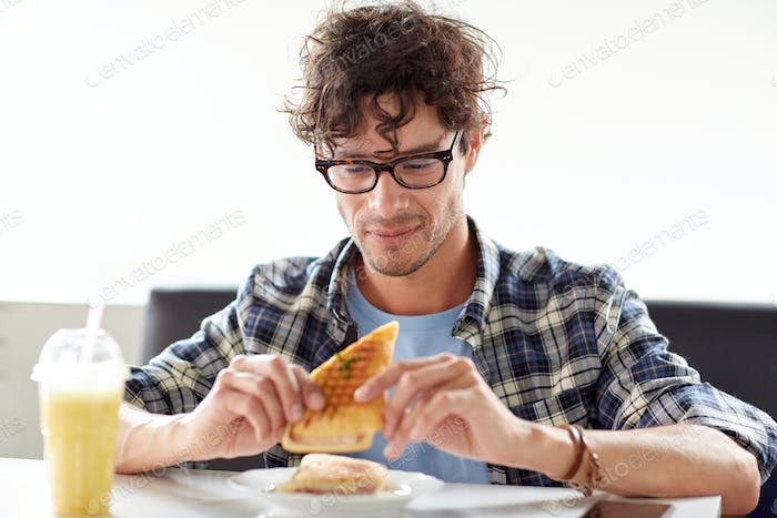 happy man eating sandwich at cafe for lunch