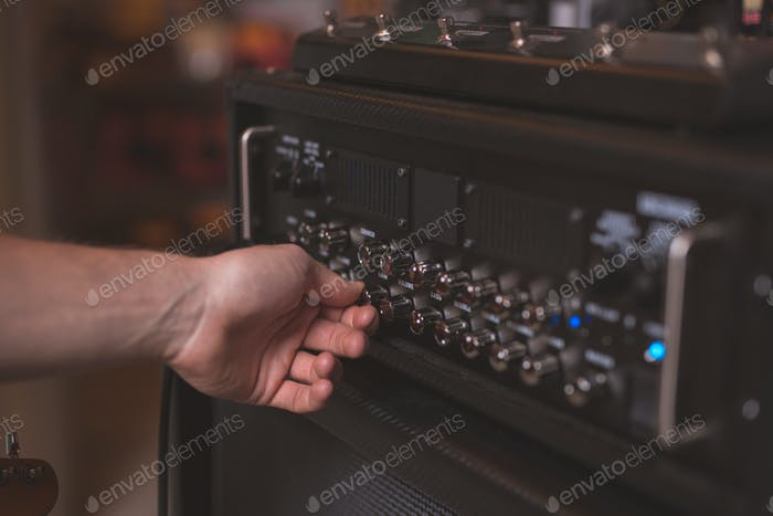 Man's hand atthe music panel
