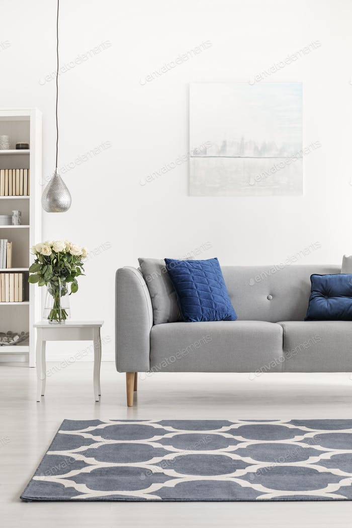 Patterned carpet in front of grey couch with blue pillows in whi