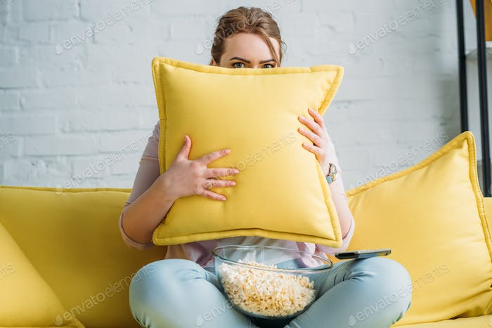 woman looking out from cushion while watching horror movie with popcorn at home
