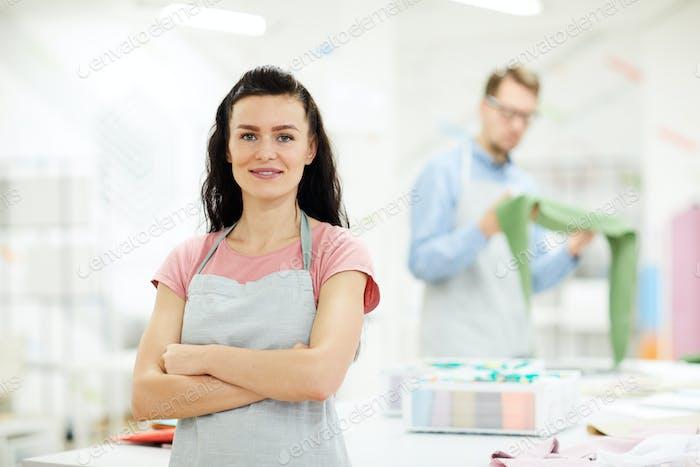 Content female dressmaker in atelier